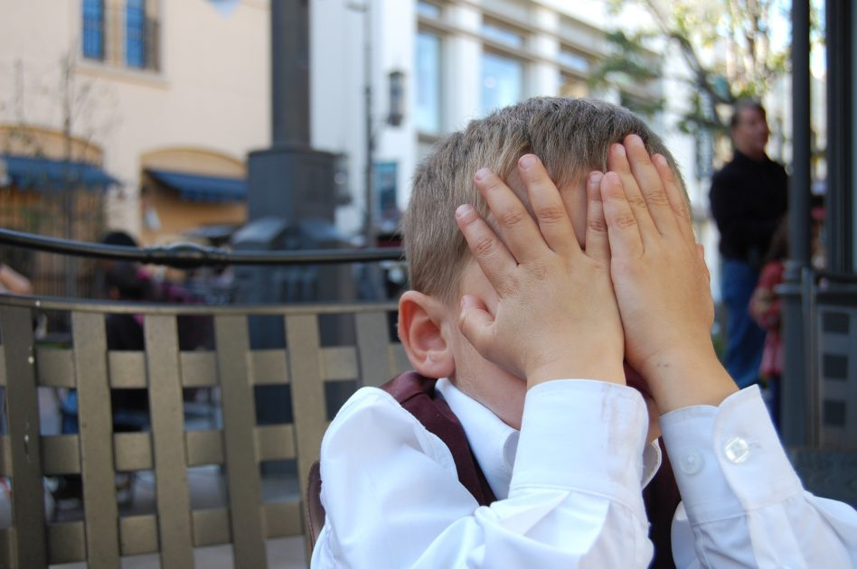 手で顔を隠す子供
